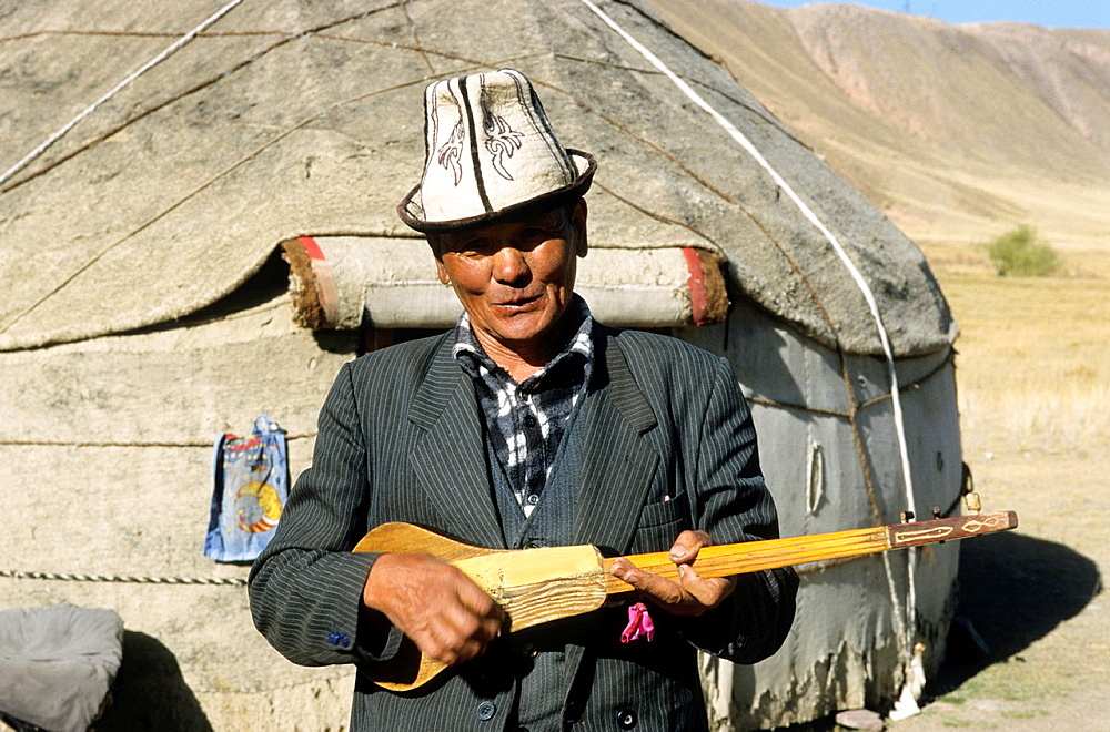 Kyrgyz Life, Nomad, a man is playing on a self made Guitar, Kyrgyzstan.