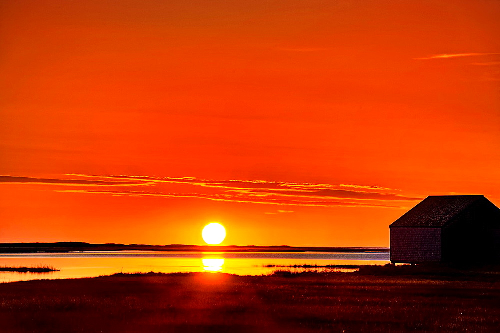 Sunrise over salt pond with boat house silhouette, Eastham, Cape Cod, MA, USA.