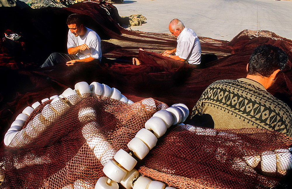 Fishermen sew the nets, in fishing port of Adra. Almeria province, Andalucia, Spain.