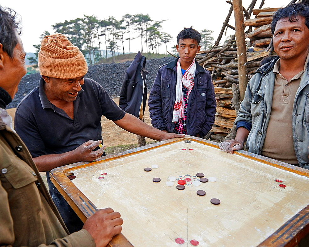 A group of men playing the Indian board game, Carrom, one of the most widely played games in southern Asia.