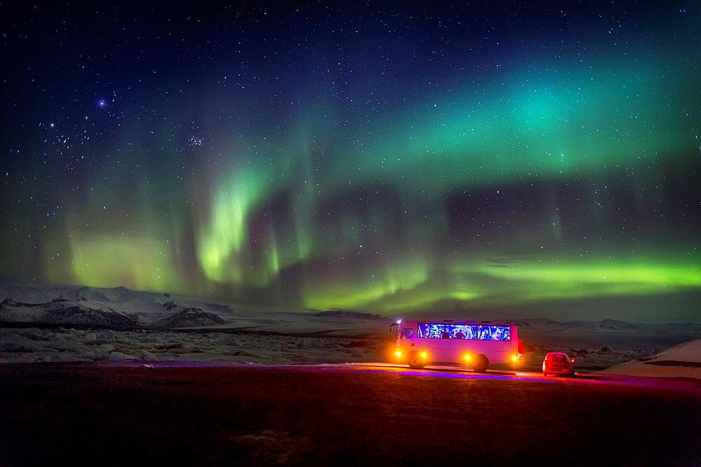 Aurora Borealis or Northern lights. Bus and car by the Jokulsarlon, Breidarmerkurjokull, Vatnajokull Ice Cap, Iceland.