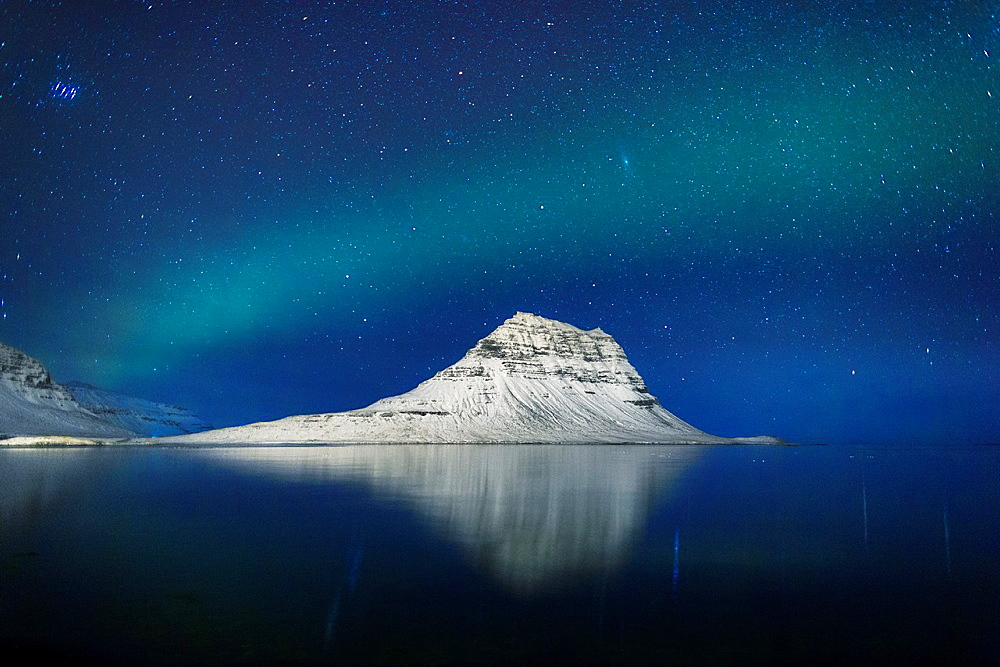 Aurora Borealis or Northern lights with the Milky Way Galaxy over fjord. Mt. Kirkjufell, Grundarfjordur, Snaefellsnes Peninsula, Iceland.