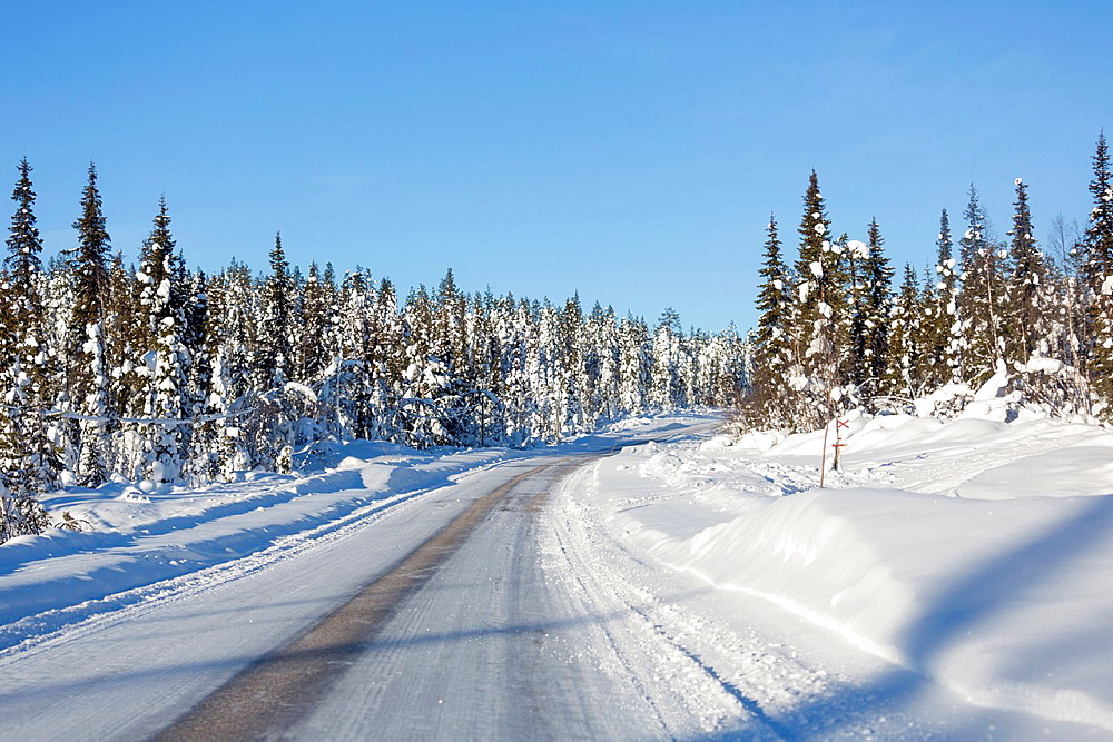 Winter road in february with snnowy trees on the side and clear blue sky in Gallivare, Swedish lapland