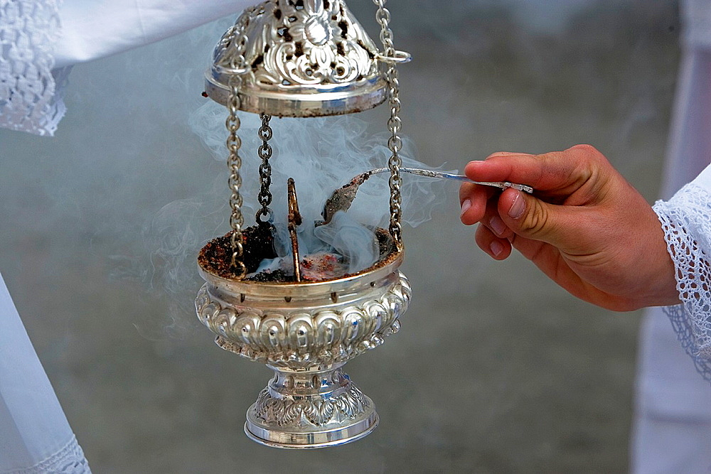 Altar boy looking with a silver spoon incense in a censer during a procession of holy week, Andalucia, Spain.
