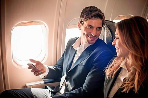Businesspeople on aeroplane with smartphone