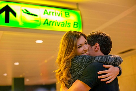Young couple hugging in airport arrivals