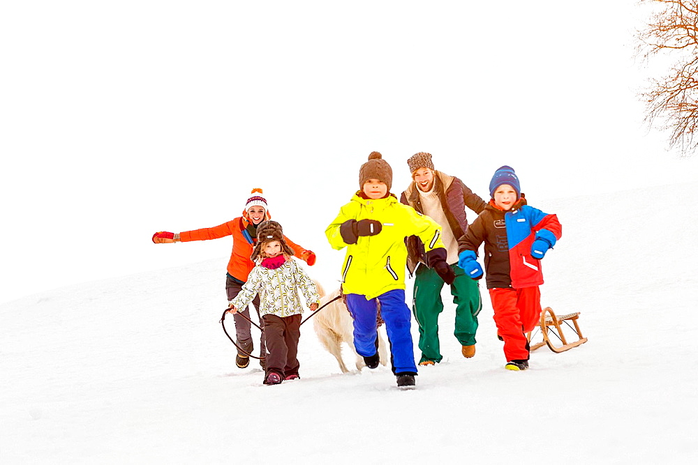 Family with three children running in snow