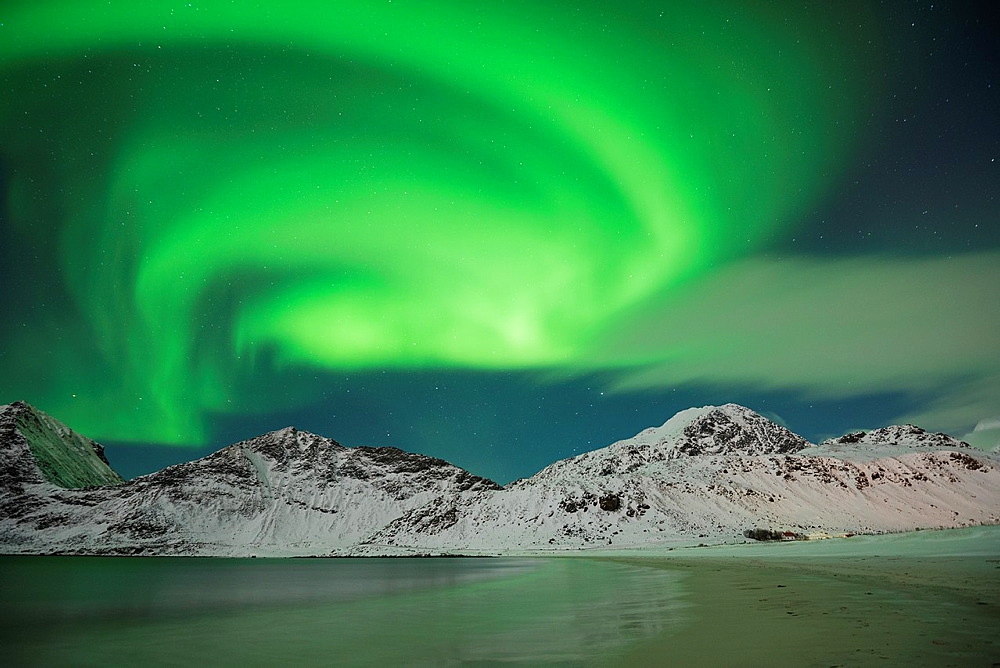 Aurora Borealis, Northern Lights shine in sky over snow covered mountains from Vik beach, VestvÂgoy, Lofoten Islands, Norway