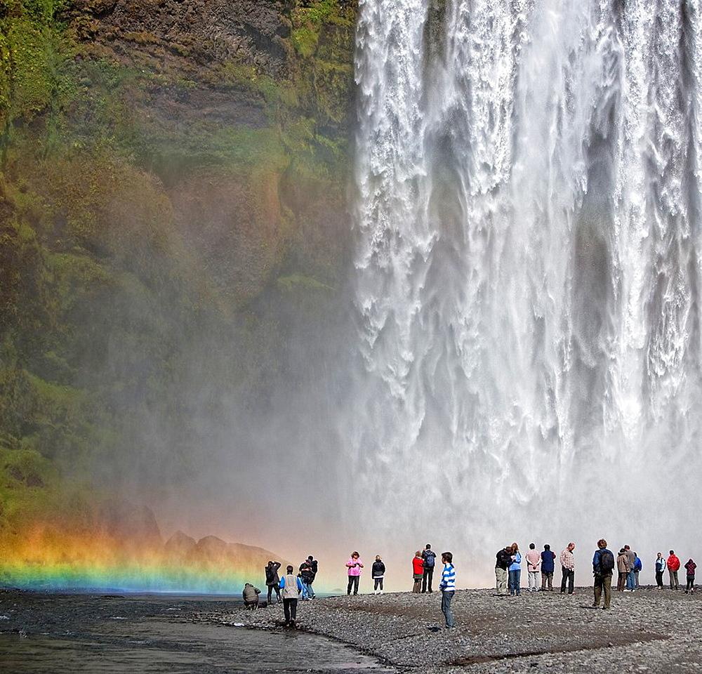 Tourist at Skogarfoss Waterfalls, Iceland.