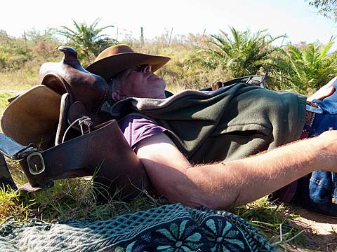 Senior man lying on back resting on saddle, Uruguay