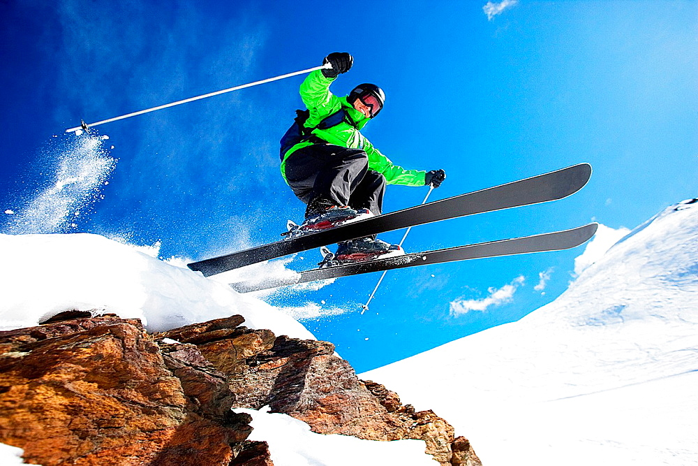 Male skier jumping at speed down mountain