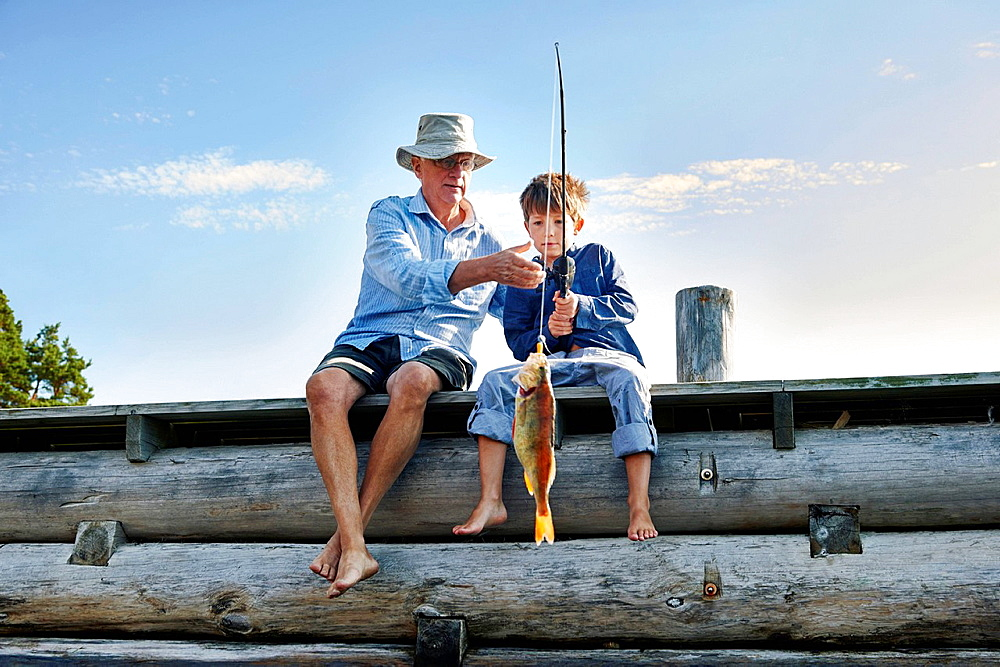 Grandfather and grandson fishing, Utvalnas, Sweden