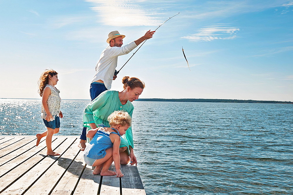 Family fishing off pier, Utvalnas, Sweden
