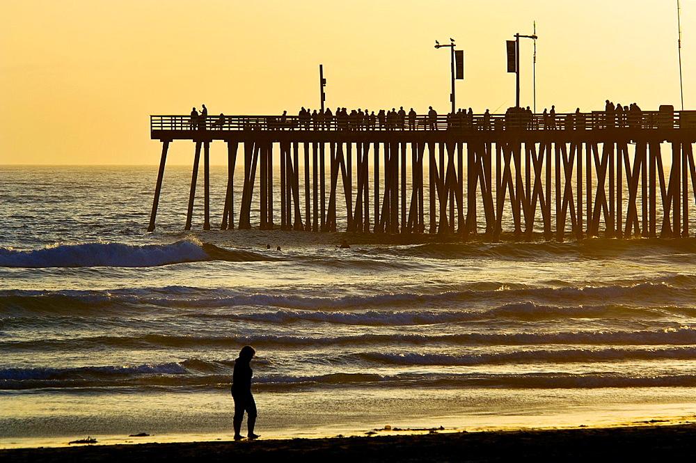 Sunset light over the pier and ocean waves at Pismo Beach, San Luis Obispo County coast, California.