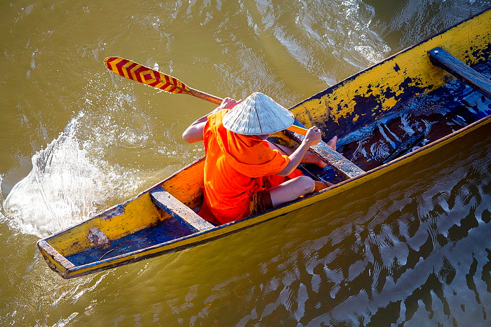 Buddhist monks on a row boat on the Mekong River in Paske, Laos.