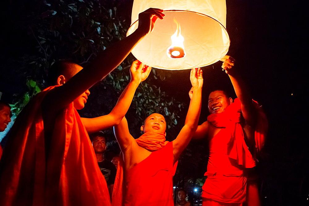 Buddhist monks lighting Chinese sky lanterns in Paske, Laos.