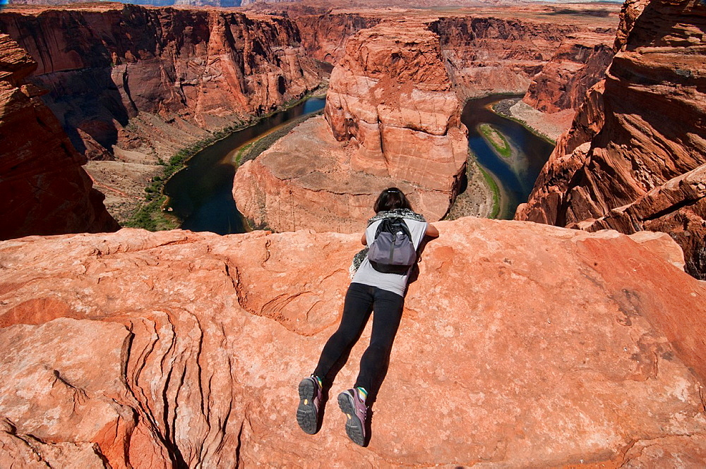 peering over the edge at Horseshoe Bend, famous meander of the Colorado River, near Page, Arizona.