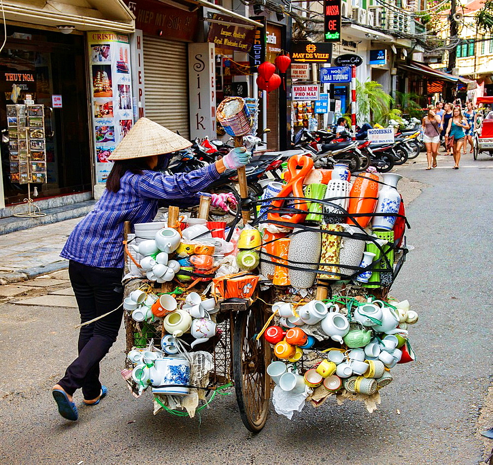 vendor pushes her load through the streets in Hanoi, Vietnam.
