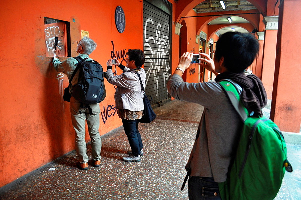 Bologna, Italy, Japanese tourists taking photos by the little window on Canale delle Moline, in via Piella