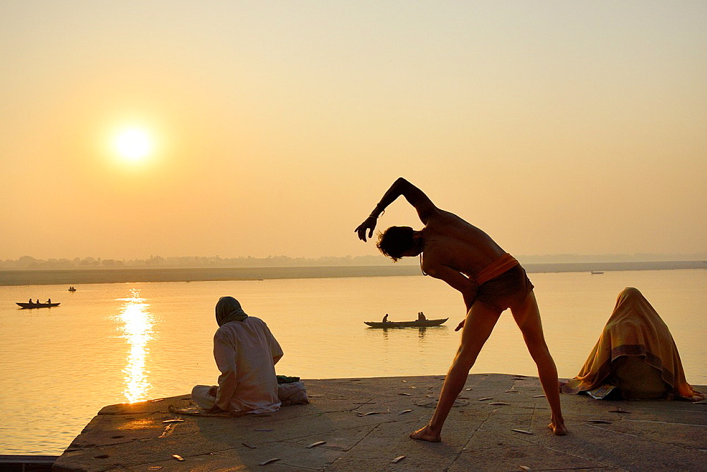 India, Uttar Pradesh, Varanasi, Yogi practising at sunrise.