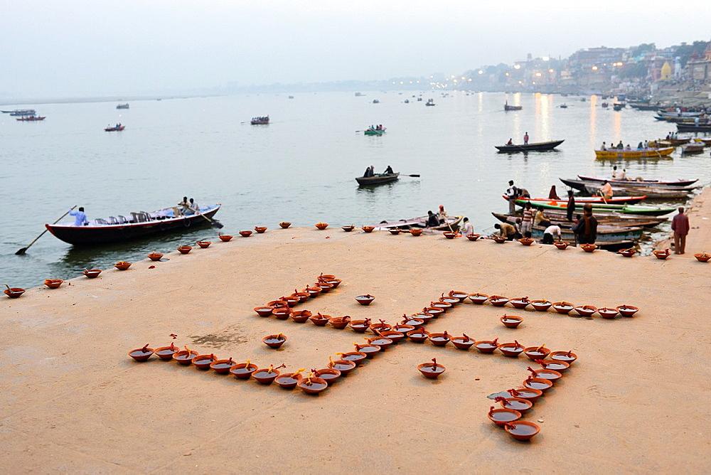 India, Uttar Pradesh, Varanasi, Swastika shaped earthen lamps set for Dev Deepawali festival.