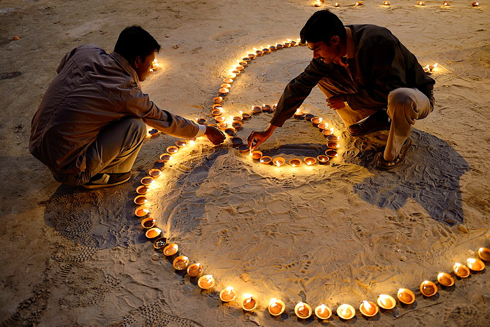 "India, Uttar Pradesh, Varanasi, Dev Deepawali festival, Hindu devotees lighting ""Om"" shaped oil lamps."