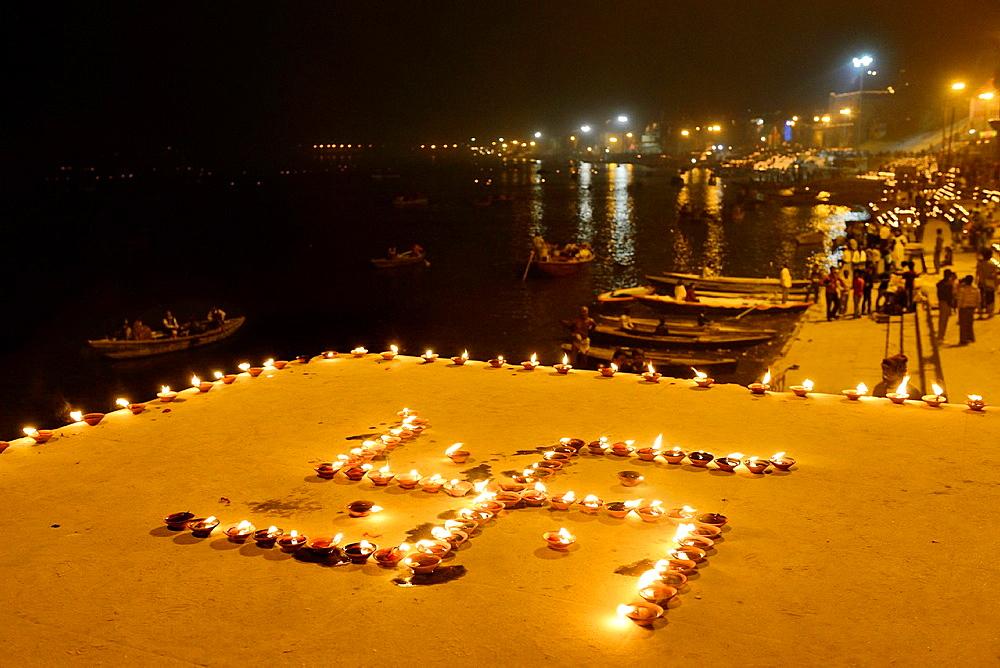 India, Uttar Pradesh, Varanasi, Swastika shaped earthen lamps lit for Dev Deepawali festival.