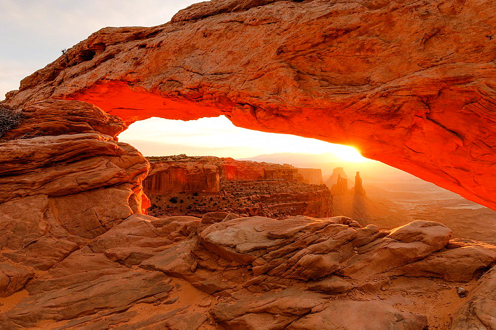 View under Mesa Arch in Canyonlands National Park at sunrise.