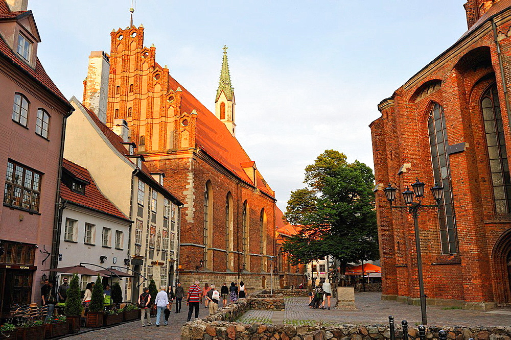 terrace of the restaurant Domini Canes facing the St. Peter' Church in Skarnu street with the St. John's Church in background, Old Town, Riga, Latvia, Baltic region, Northern Europe.