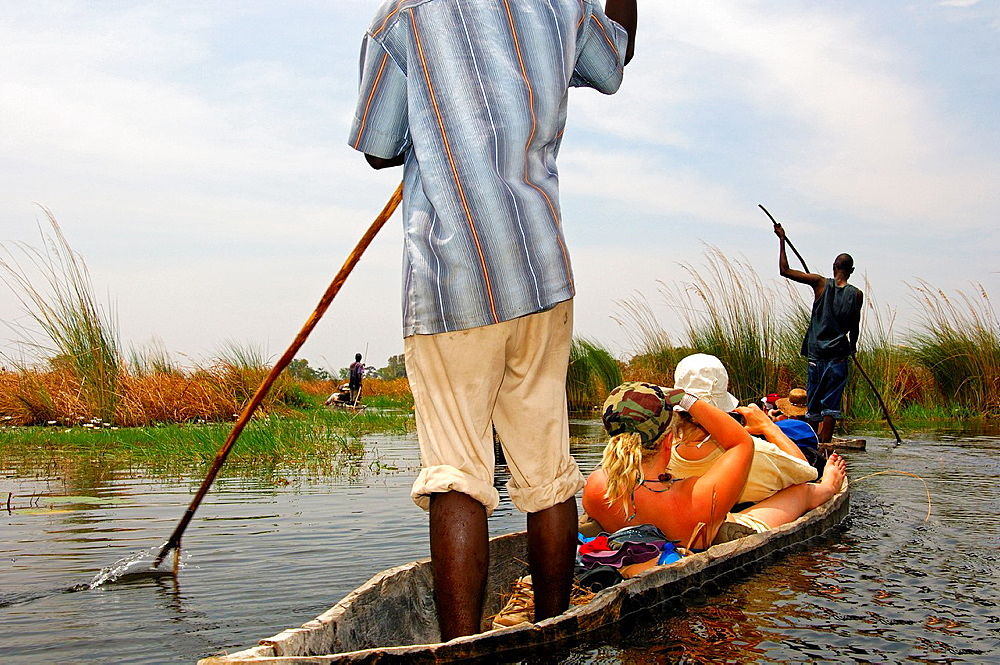 Tourists on trip in a Mokoro canoe in the Okavango Delta, Botswana.