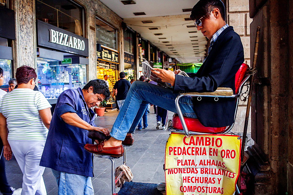 Shoeshine man and client, in Plaza de la Constitucion,El Zocalo, Zocalo Square, Mexico City, Mexico.