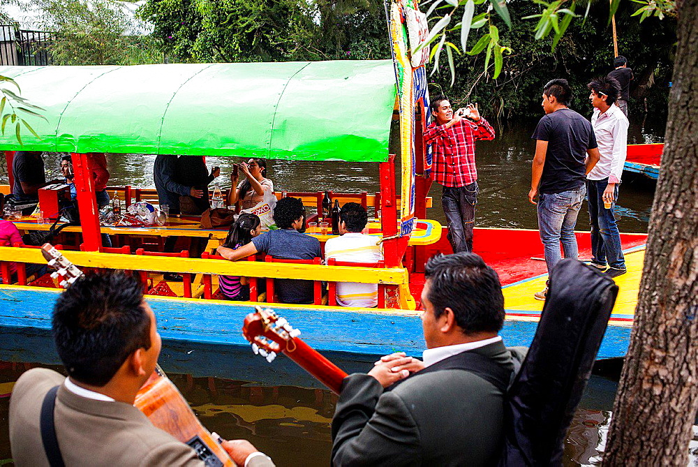 Musicians waiting to be hired and Trajineras on Canal, Xochimilco, Mexico City, Mexico.