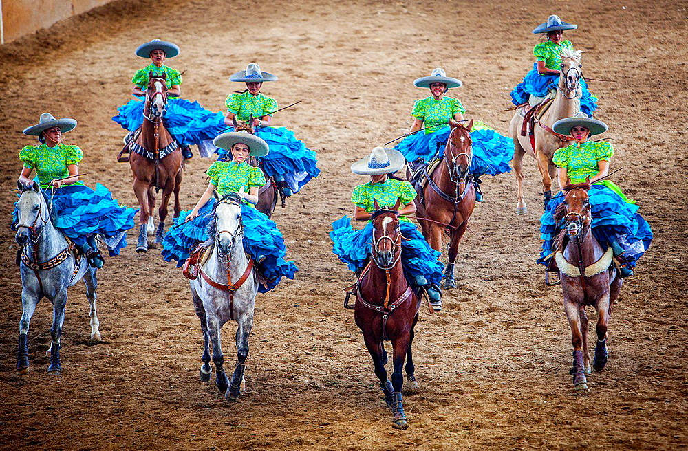 Escaramuzas ride their horses. A charreada Mexican rodeo at the Lienzo Charro Zermeno, Guadalajara, Jalisco, Mexico. - 817-455915