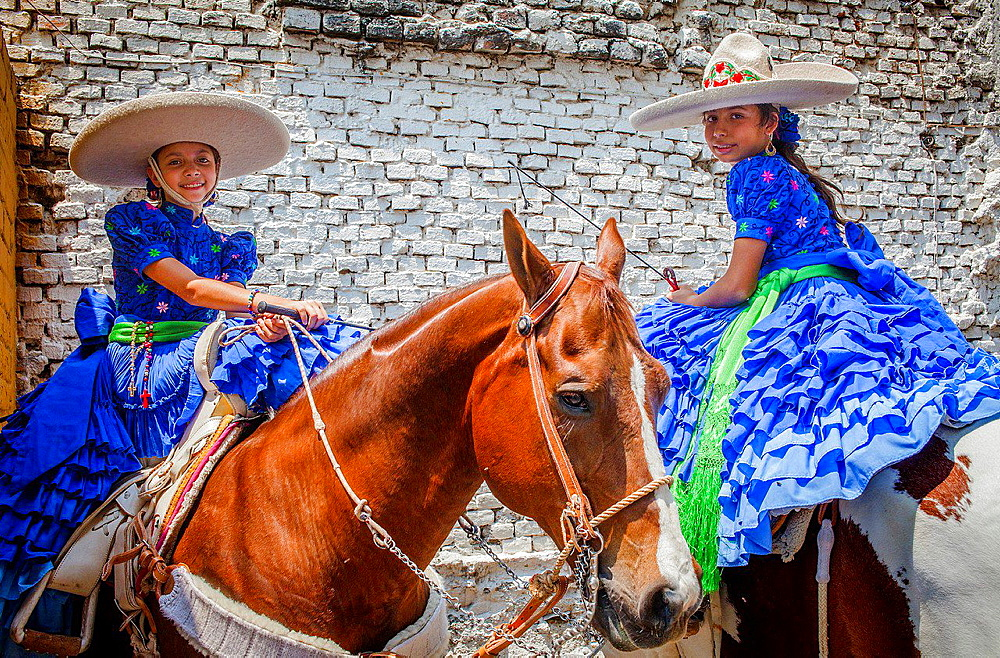 Escaramuzas ride their horses. A charreada Mexican rodeo at the Lienzo Charro Zermeno, Guadalajara, Jalisco, Mexico. - 817-455921