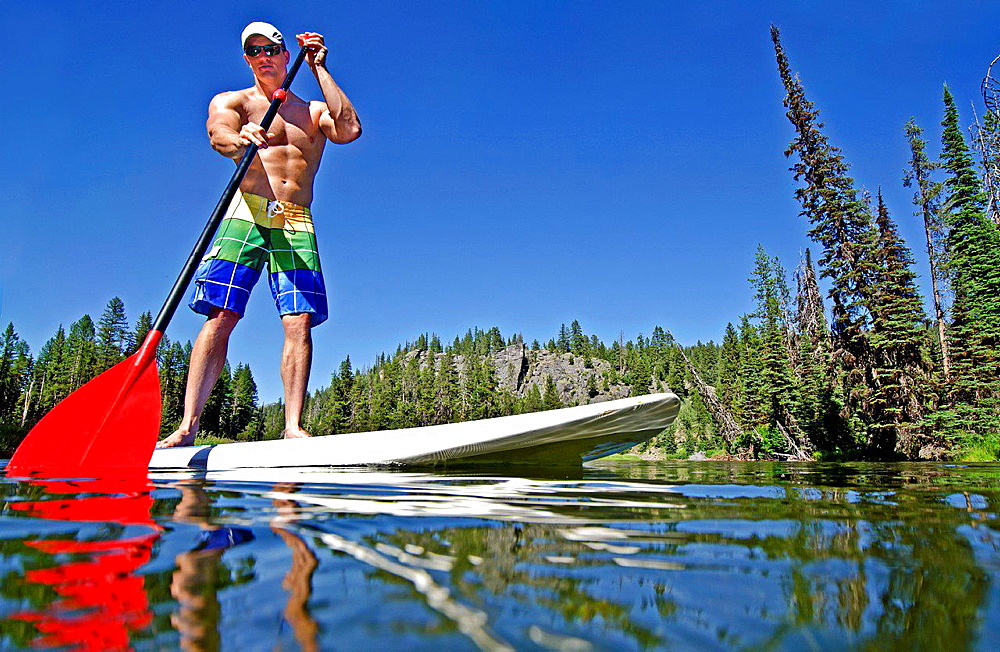 riding the Stand Up Paddle Board on the North Fork of the Payette River near Payette Lake and the city of McCall in the Salmon River Mountains of central Idaho.