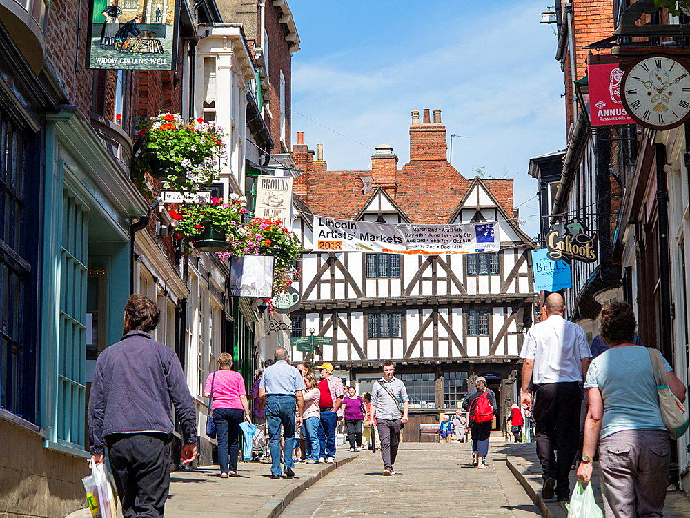 Steep Hill with people shopping and half-timbered building at top, Lincoln, England.