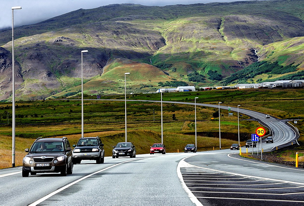 Cars on a highway located in mossy lava fields of Western Regions of Iceland