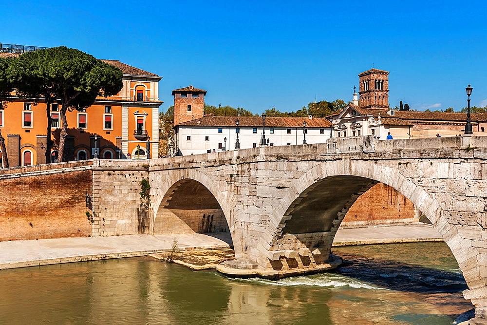 View over the Tiber river to the bridge Ponte Cestio, to island Isola Tiberina and to Basilica of St. Bartholomew on the Island Sancti Bartholomaei in Insula, Rome, Lazio, Italy, Europe.