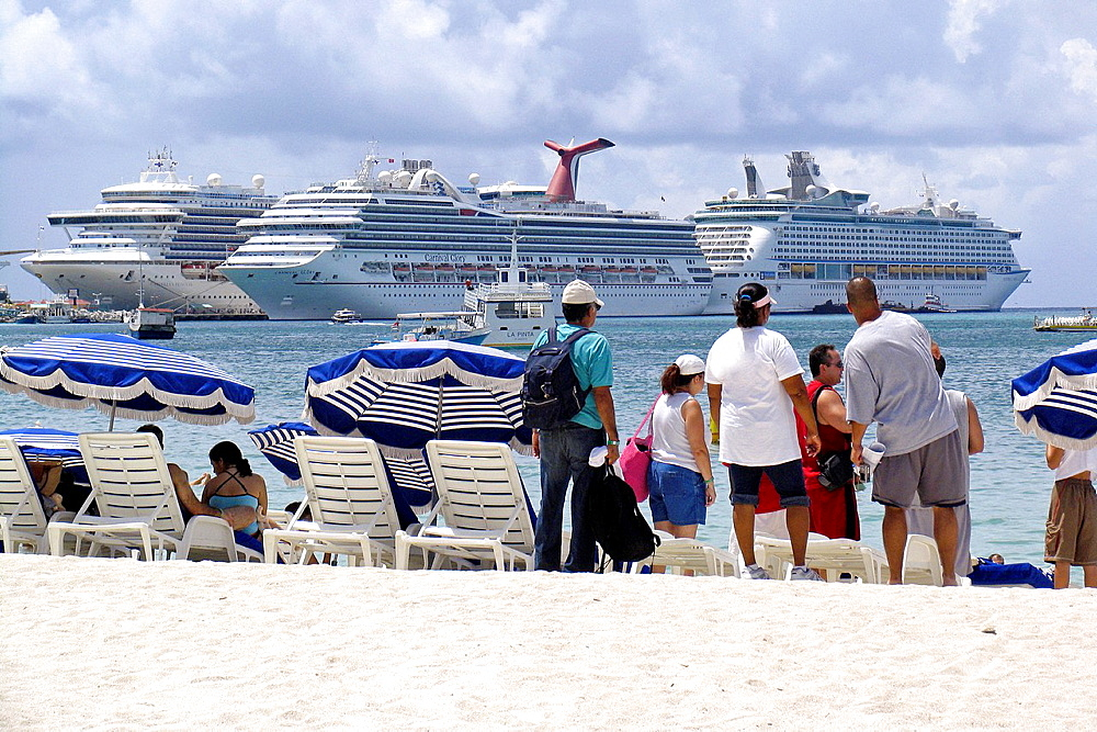 Visitors on Great Bay beach Philipsburg with three cruise ships docked in background St Maarten - 817-459250