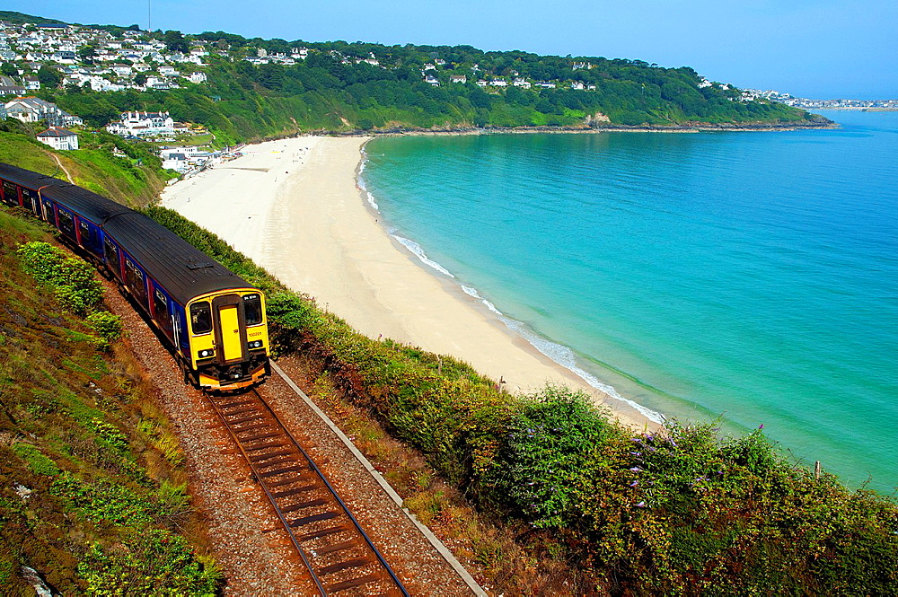a train leaves st.ives along the coastal track in cornwall, england, uk.