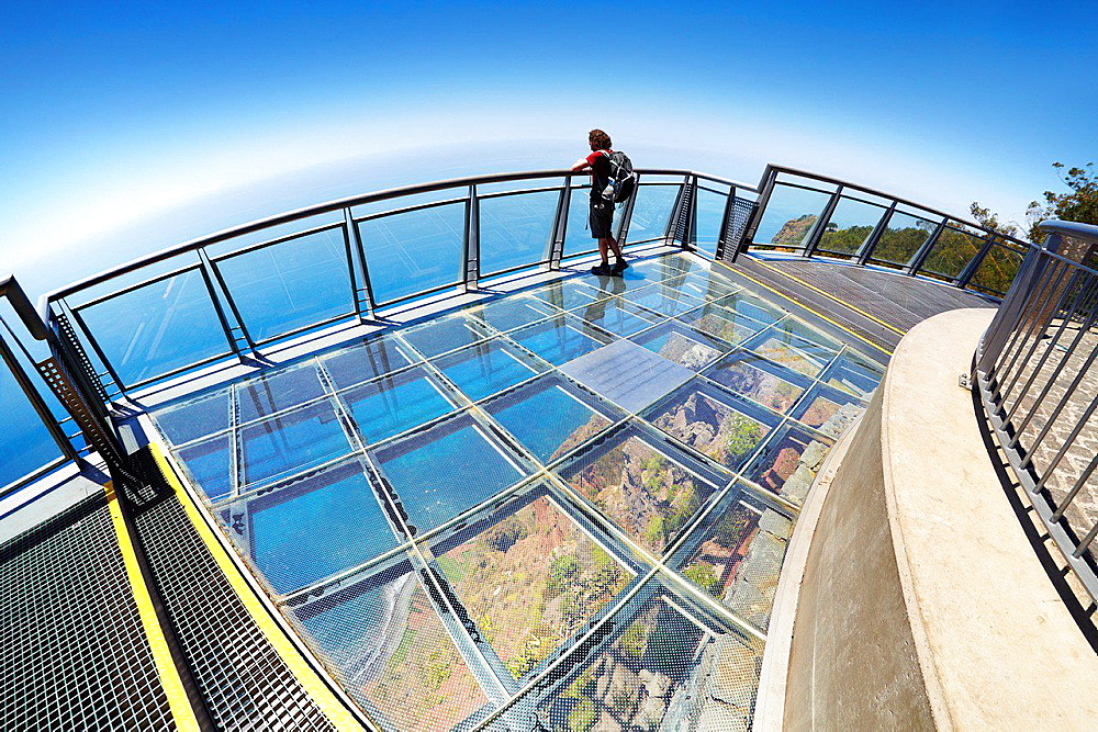 Tourist on the panoramic terrace (with glass floor) at the top of Cabo Girao (580 m highest) cliff, Camara de Lobos, Madeira, Portugal.