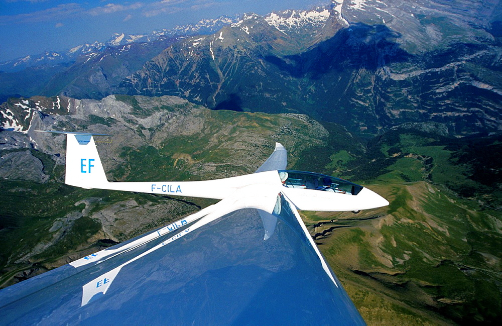 Glider plane Duo Discus flying over Las Blaneas mountains, Aragon, Spain.