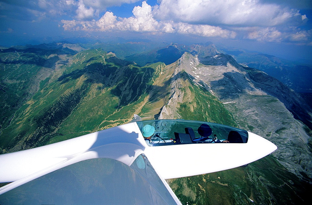 Glider plane Duo Discus flying over Bisaurin mountains, Aragon, Spain.