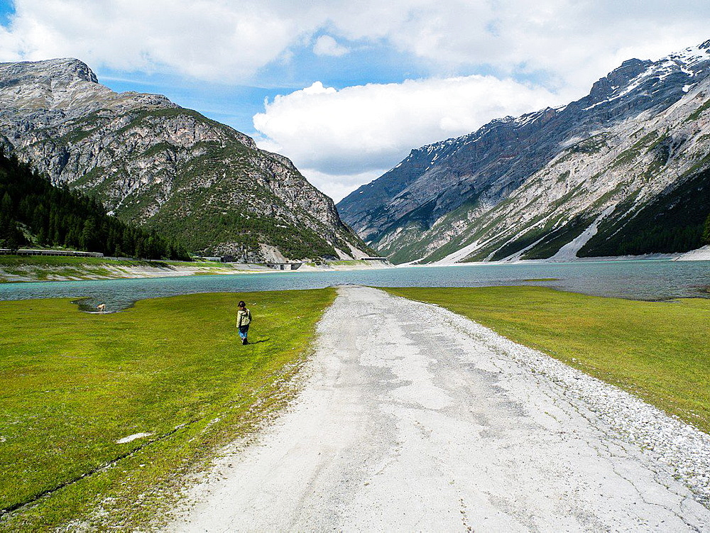 Child near the road that disappears into the lake of Livigno, Livigno, Lombardy, Italy