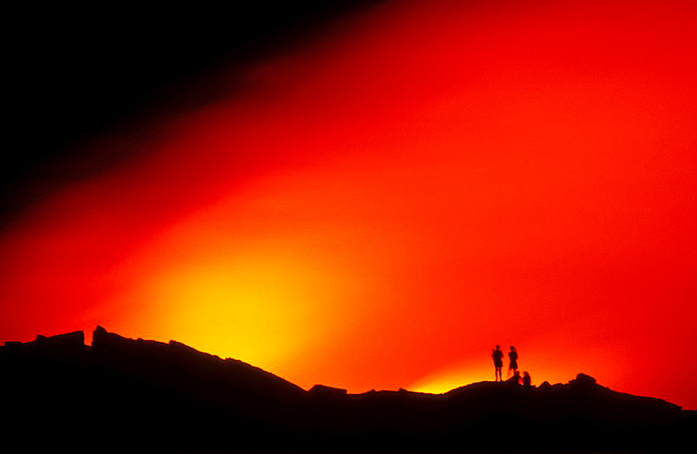 Hikers watching lava flow enter the Pacific Ocean at night, Hawaii Volcanoes National Park, The Big Island, Hawaii USA.