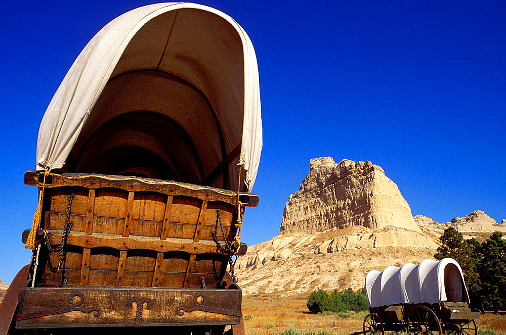 Conestoga wagons under Eagle Rock on the Oregon Trail, Scotts Bluff National Monument, Nebraska USA.