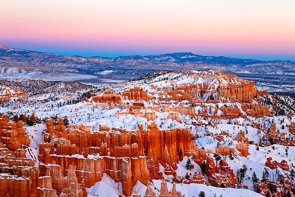 Hoodoo rock formations and snow at sunset, Bryce Amphitheater, Bryce Canyon National Park, Utah, United States of America.