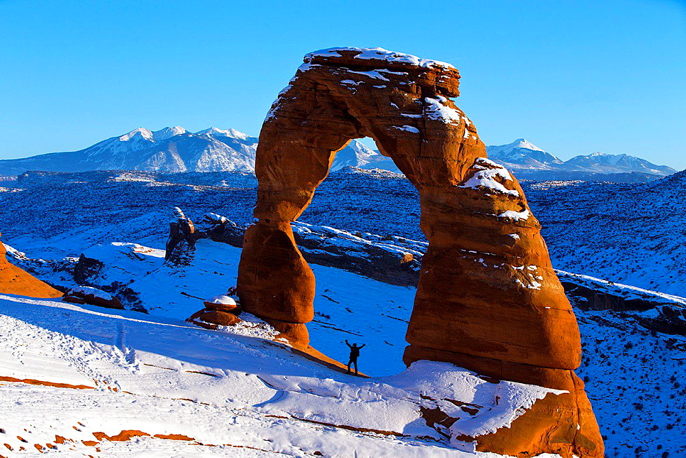 A person standing with arms up under Delicate Arch with snow in winter at sunset, Arches National Park, Utah, United States of America.