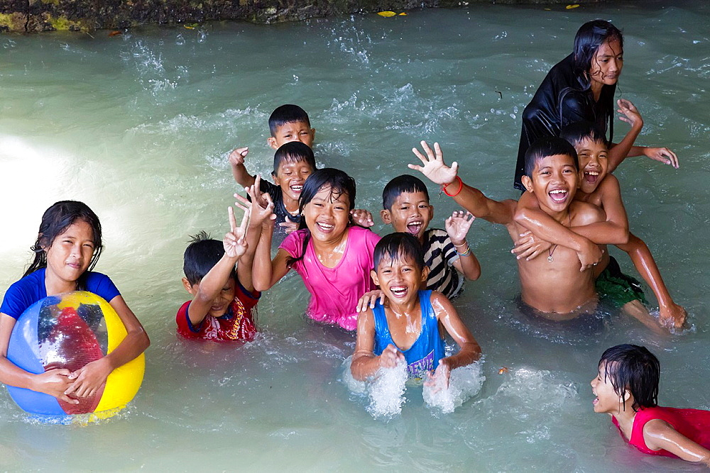 Young local Children enjoying a Bath in a Pool in Tagbilaran on Bohol Island, Philippines.