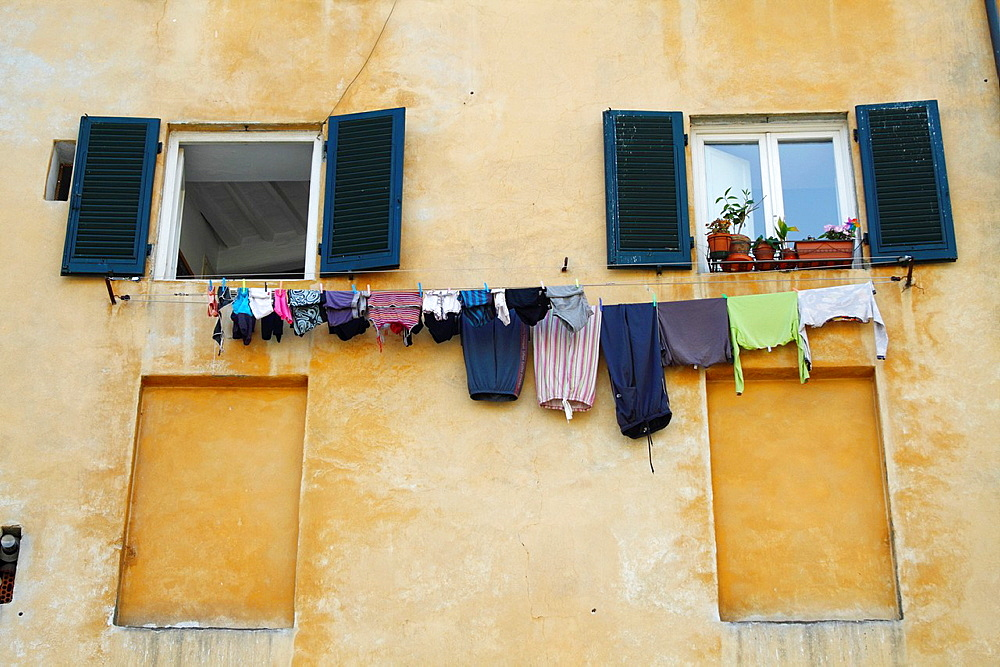 Clothes hung out to dry on an exterior Wall in Lucca in Tuscany, Italy.